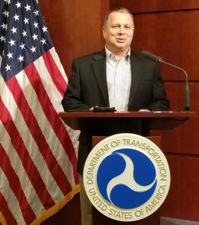 Cory Hutchinson standing at USDOT podium