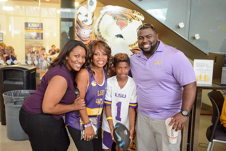 smiling group in purple and gold standing in front of a Mike the Tiger cutout
