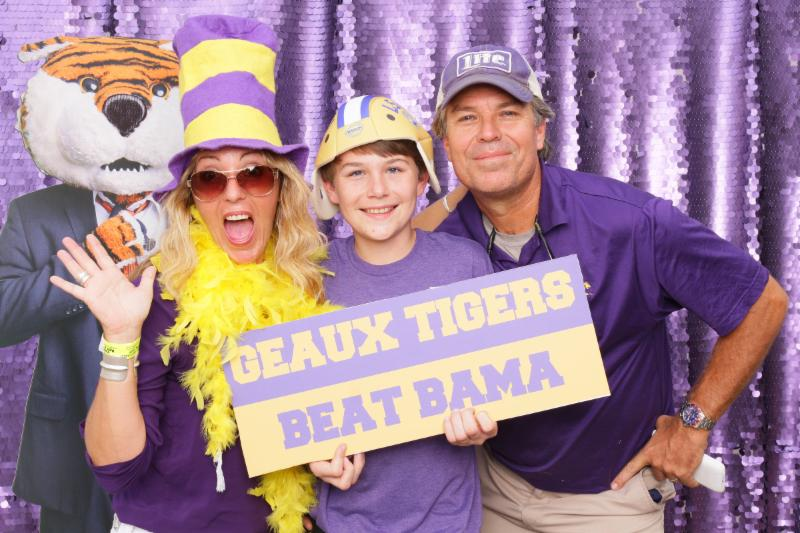 happy family holding a Beat Bama sign