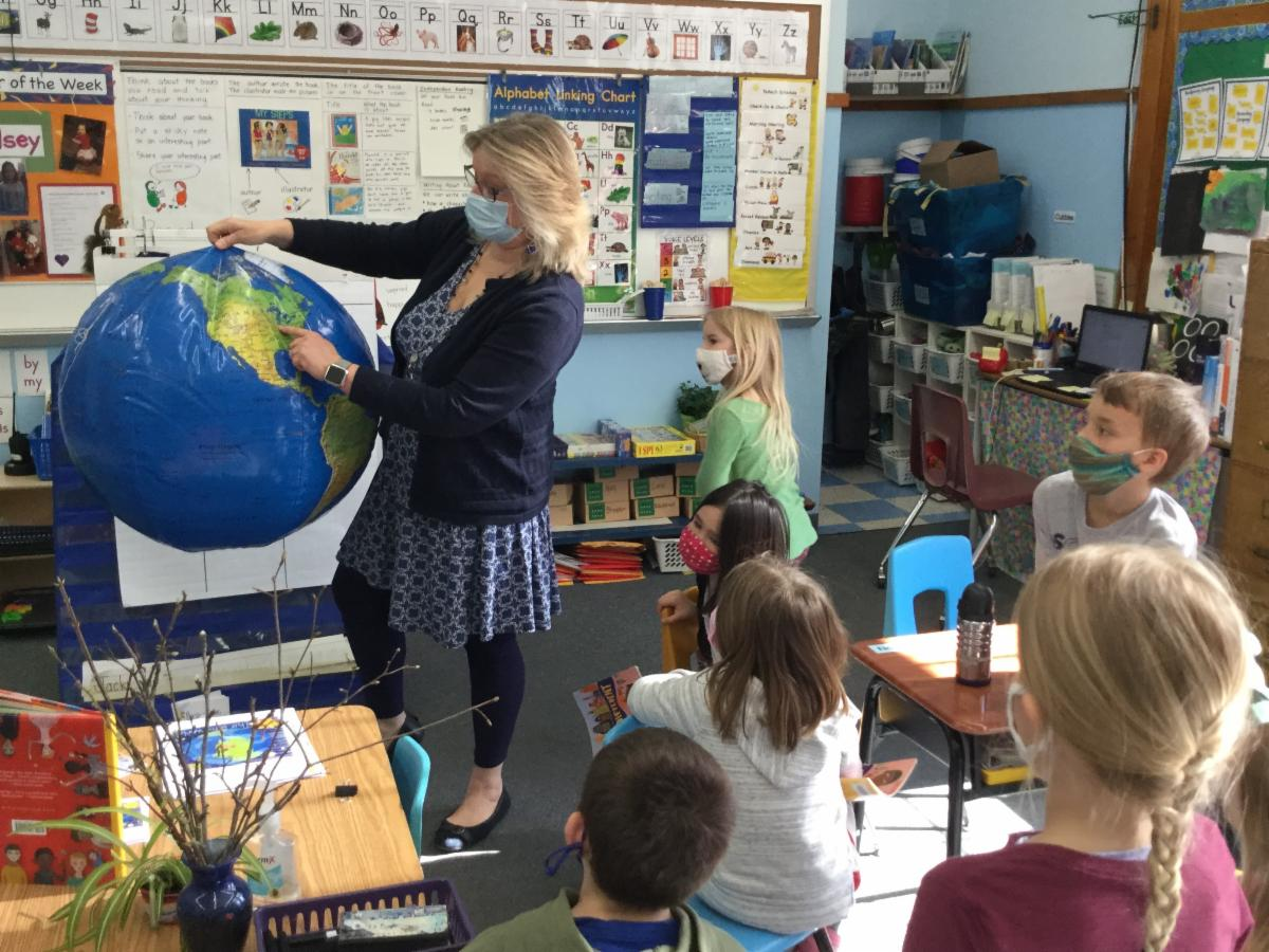 Mrs. White shows kindergarten places on the globe