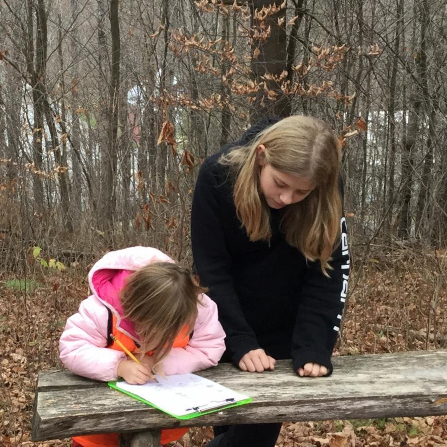 Bianca helps a kindergartner in the Outdoor Classroom during Forest Day.