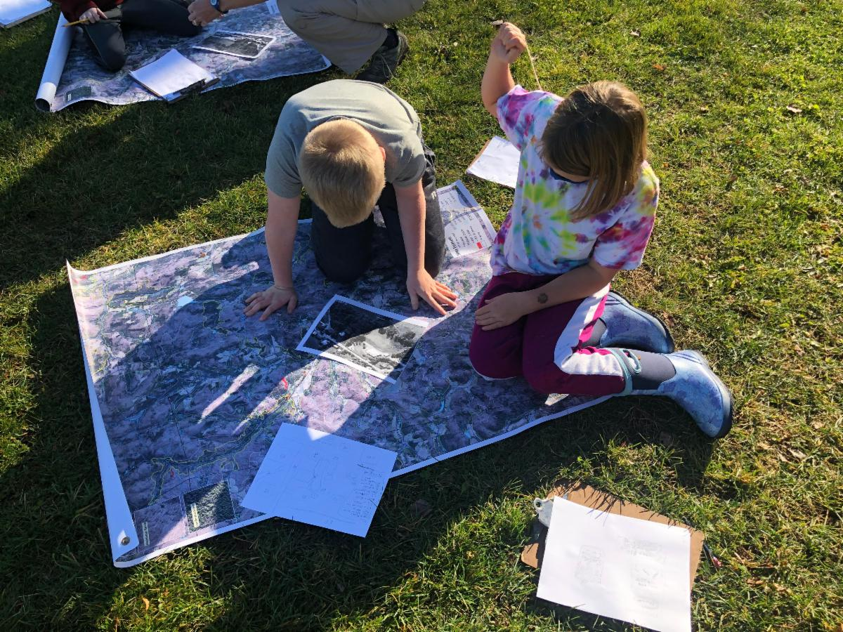 Fourth grade students work on identifying areas on a large map of Strafford.