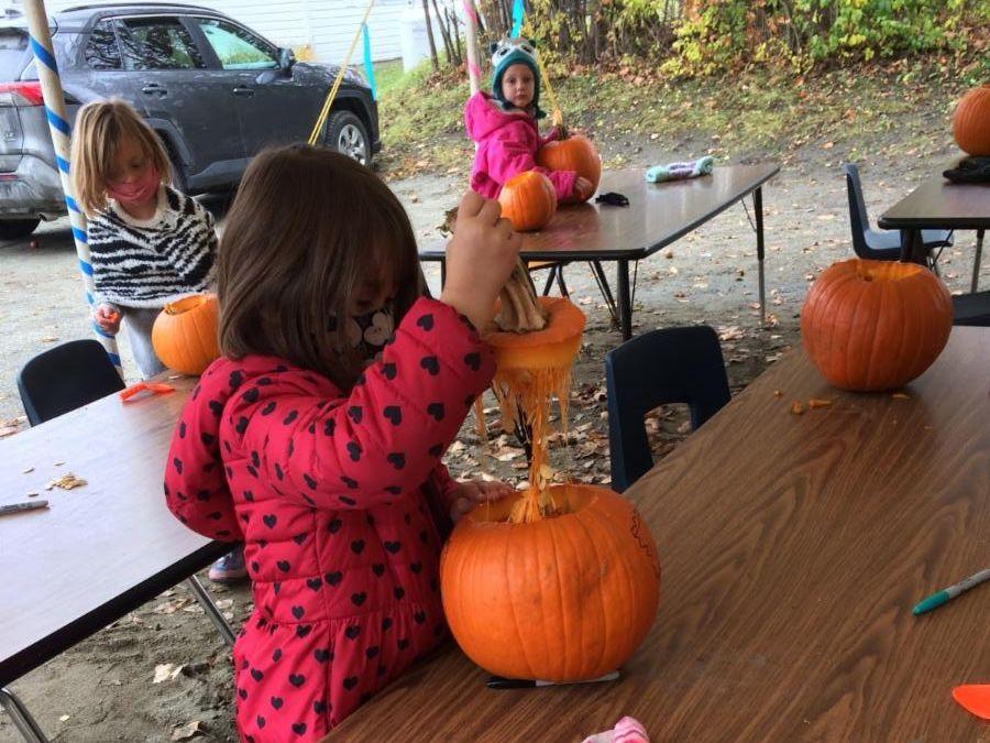 First graders carve their pumpkins.