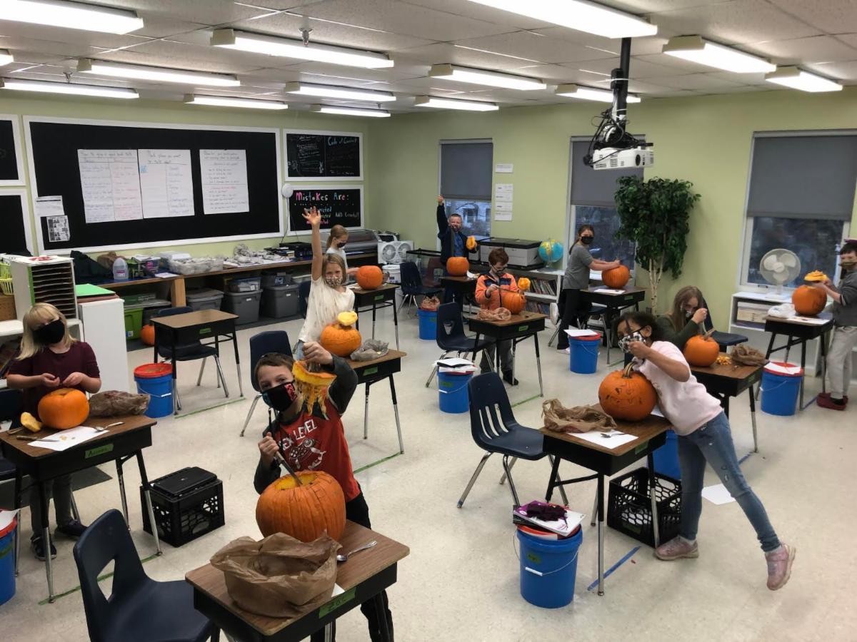 Fourth graders show of their jack-o-lanterns.