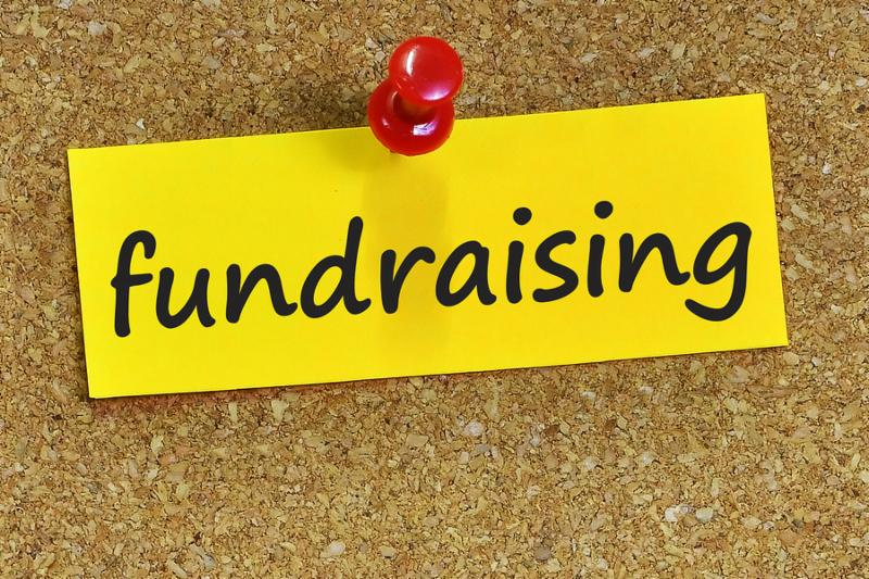 fundraising word on yellow notepaper with cork background.