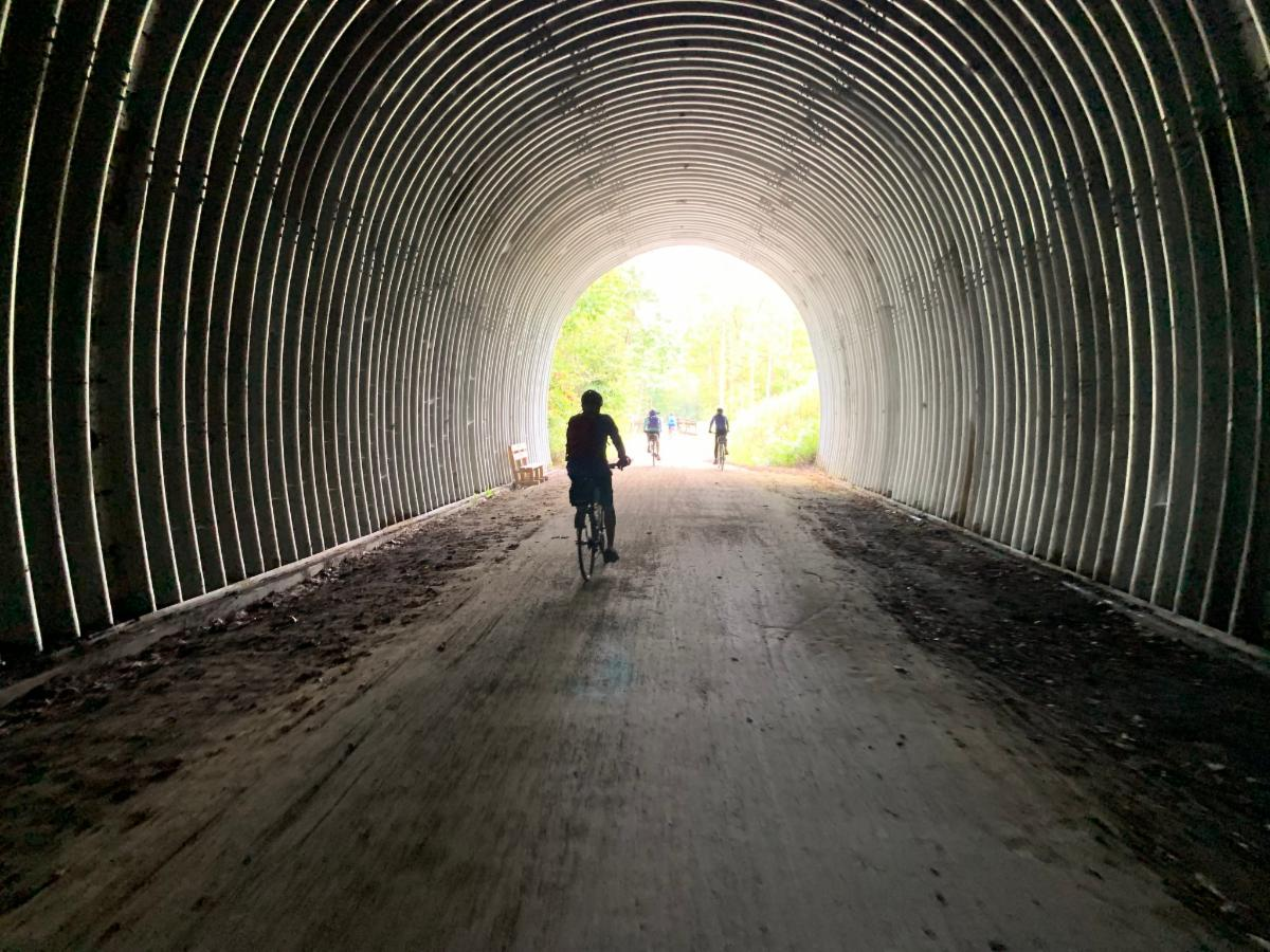 man biking through a tunnel with the sun shining at the end