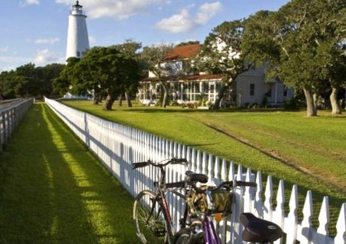 Bike resting along a fence, with a lighthouse in the distance