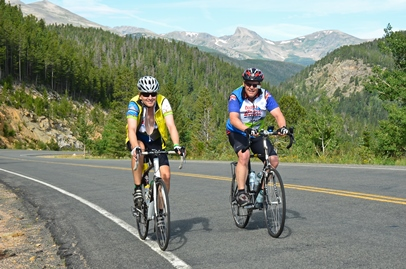Two men riding bikes on a paved road with mountains in the distance.