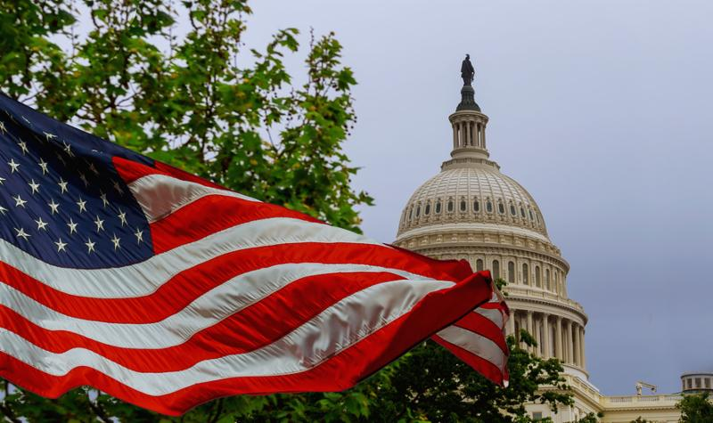 The US Capitol building with a waving American flag superimposed on the sky Capitol Hill in Washington DC