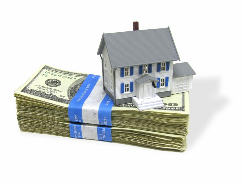 model of house sitting on stack of dollar bills