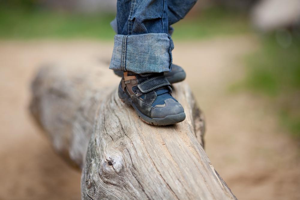 child walking on a log