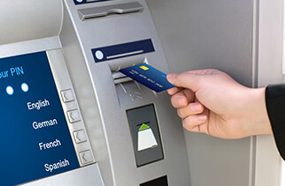 Person inserting debit card into an ATM machine at a bank