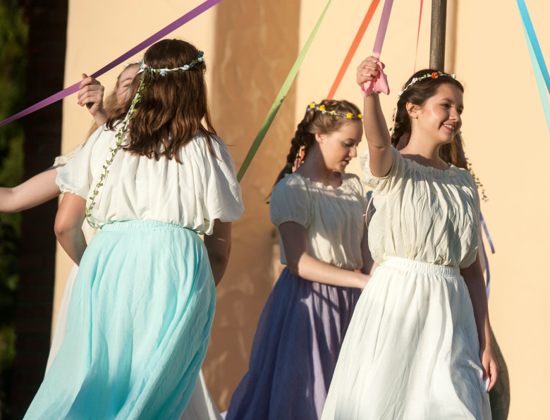 Students dance around the maypole for a scene in a play