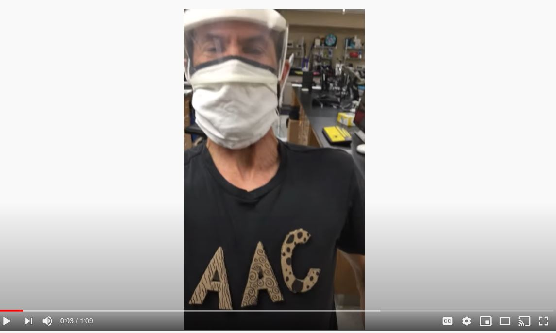 Scout wearing a face shield face mask and a t-shirt that reads AAC