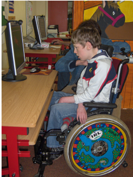Boy positioned in a wheelchair in front of a desktop computer