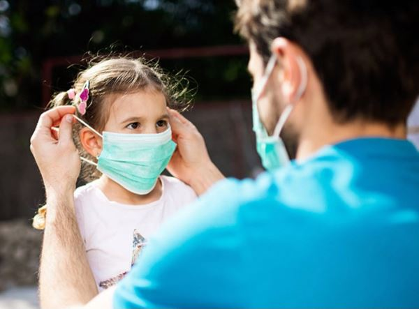 Image of young child having help putting on a protective mask