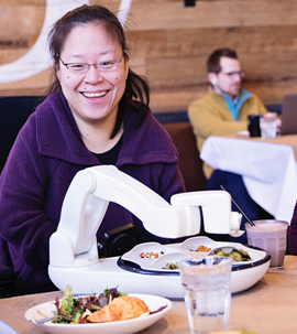 A smiling woman positioned in a wheelchair in front of the Obi Feeder full of food in a restaurant.