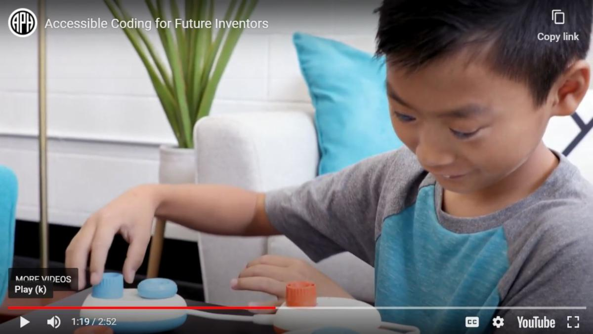 Young boy with blindness programming computer code with tactile manipulatives
