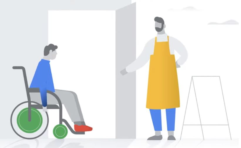 Shop owner welcomes guest who is accessing a  doorway by navigating a manual wheelchair.