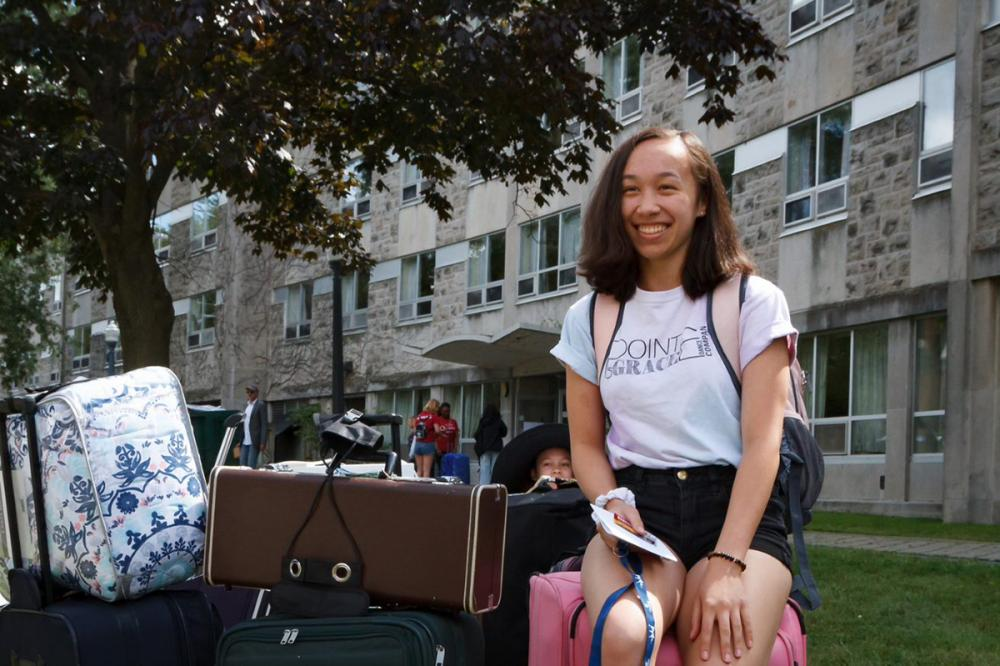 student on suitecase move-in