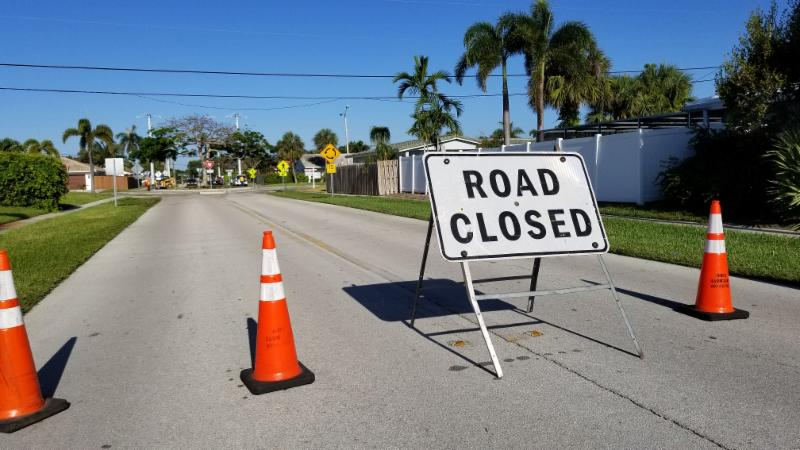 """traffic cones blocking street with """"road closed"""" sign"""