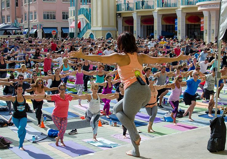 large group of people doing yoga in mizner park
