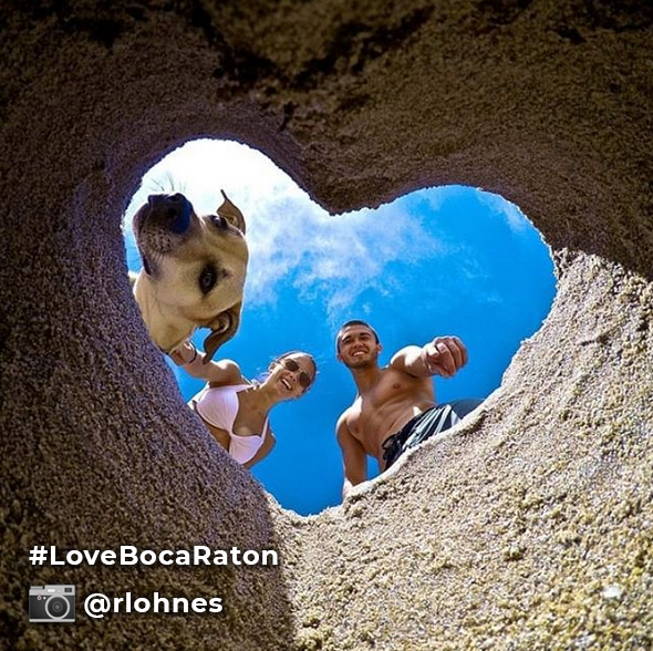 Love Boca Raton hashtag instagram picture from @rlohnes of owners and dog looking through heart-shaped hole in sand