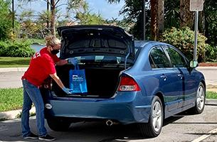 Boca Raton Public Library staff wearing a mask and putting books in the trunk of a car during curbside pickup