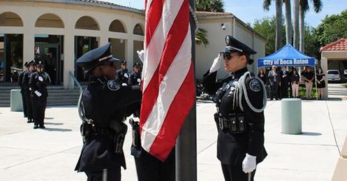 Boca Raton police saluting the american flag at a memorial service