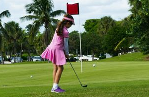 Little girl putting at golf course