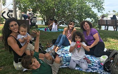 moms and children on blanket in the park enjoying food and smiling