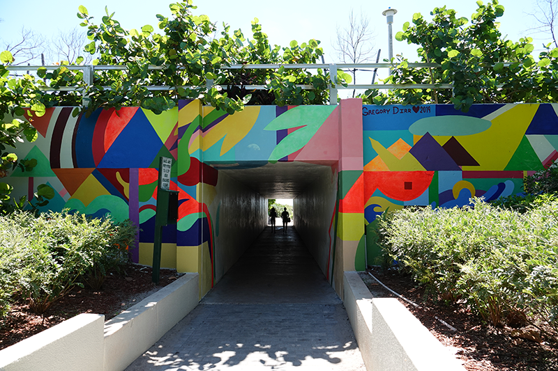 people walking in Spanish River Beach south tunnel with art mural on walls