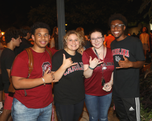 """Students give the """"Spurs Up"""" sign as they enjoy First Night Carolina."""