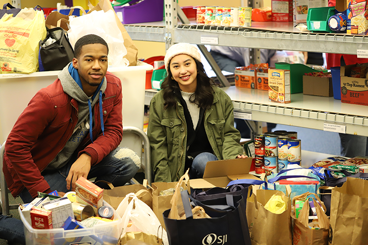 Two Rowan students with non-perishable food donations at The SHOP