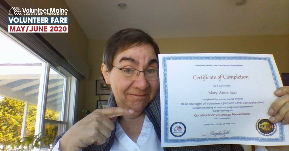 A woman poses for a webcam photo of herself holding an educational certificate.