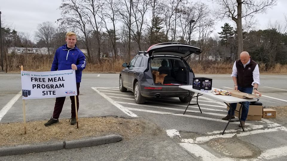On the left, a high-school age male poses in a parking lot behind a sign that reads Free Meal Program Site while an adult male on the right begins to set up a table for supplies