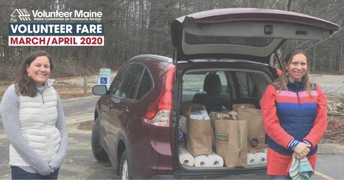 Two women stand several feet apart in front of an suv with a trunk full of supplies