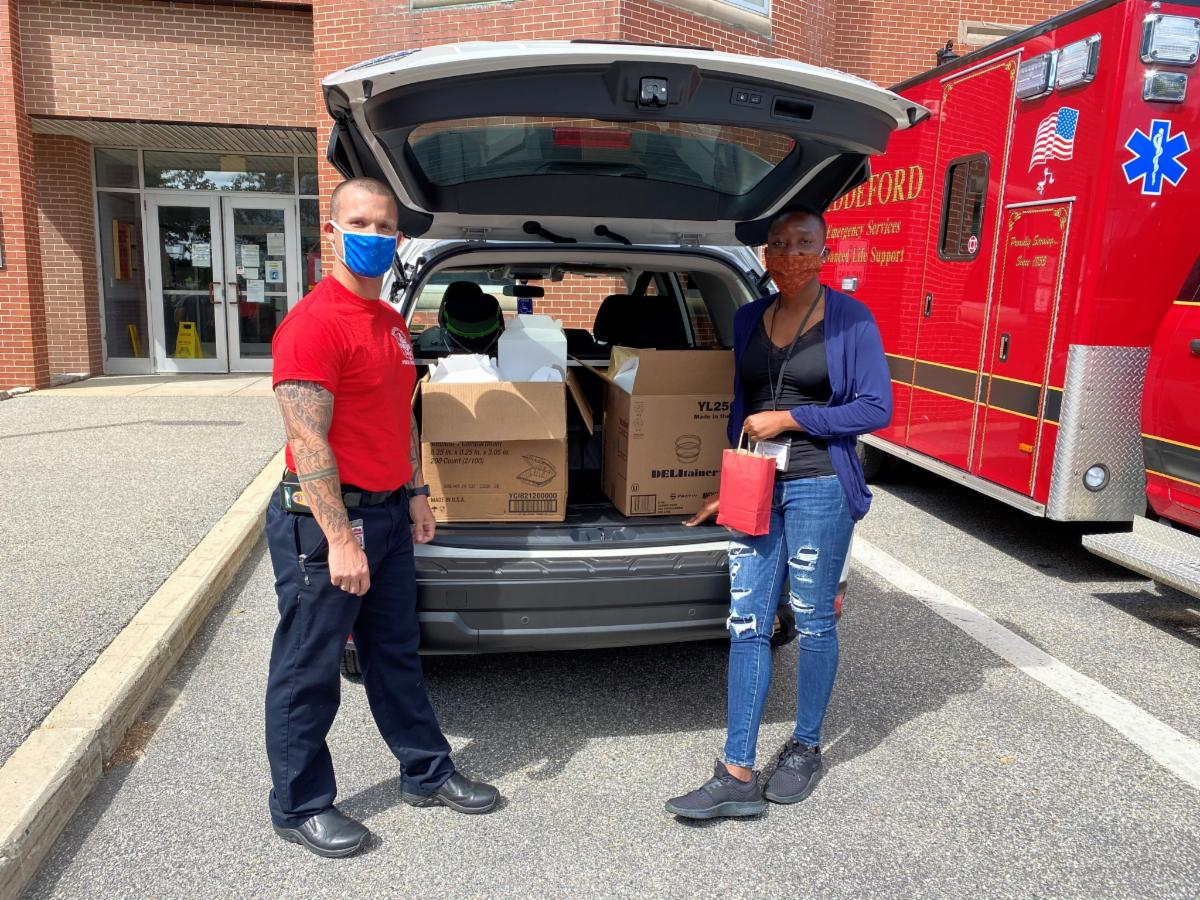 Photo of two individuals standing in front of an open full trunk full of supplies.
