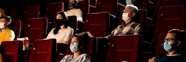 People sit inside a theater maintaining social distance while wearing masks