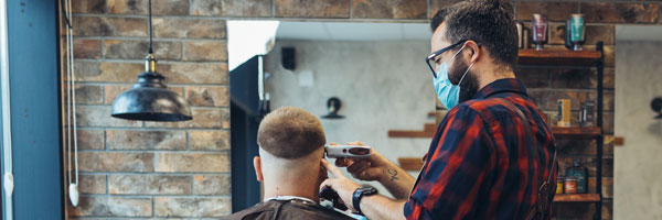 a barber cuts a clients hair while wearing a face mask