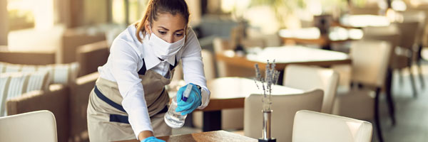 a waitress sanitizes a table in a restaurant while wearing a face covering and gloves