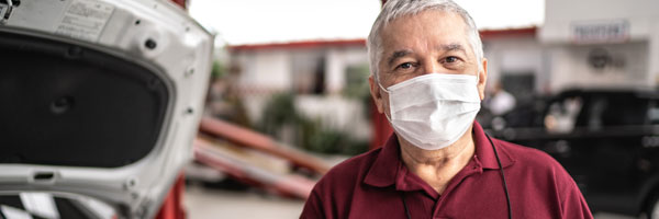 auto mechanic man with face mask at auto repair shop