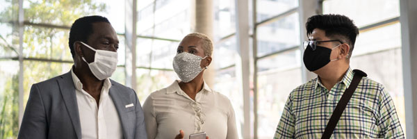 Coworkers walking and talking at office's lobby wearing face masks