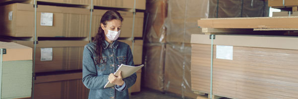a woman stands in a warehouse while recording inventory in her notebook