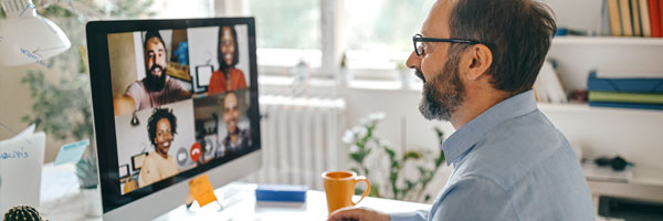 a man sits in his home office talking to coworkers on a video conference