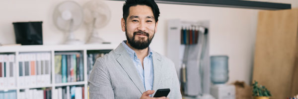 a man standing in an office smiles at the camera while holding a smart phone