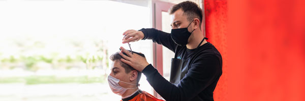 a man gives a hair cut to a male client with both wearing masks