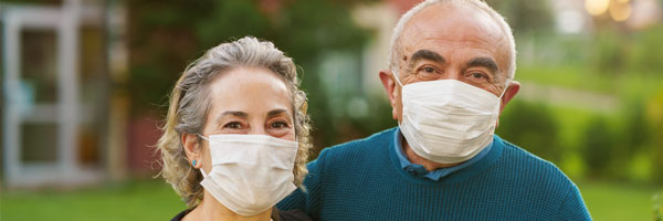 Senior couple on front of their house wearing face coverings