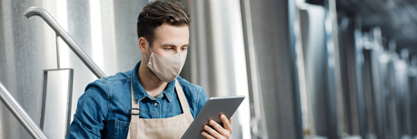 intern in apron and protective mask uses tablet in a food manufacturing warehouse