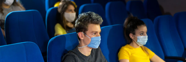 people sit in a theater while maintaining social distance and wearing masks